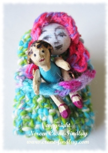 Tiny Thumbelina Finger Puppet cuddles an even tinier wooden doll carved by Noreen Crone-Findlay